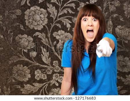 woman screaming and pointing finger, floral wallpaper - stock photo