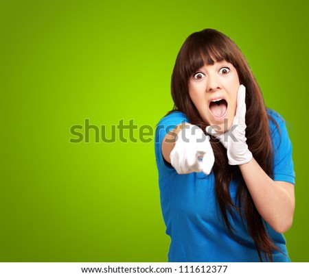 woman screaming and pointing finger isolated on green background - stock photo