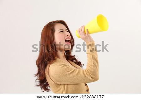 Woman screaming into bullhorn - stock photo