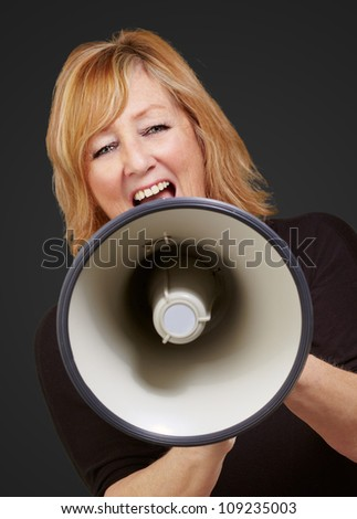 Woman screaming on a megaphone isolated on black background - stock photo