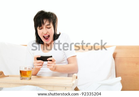 Woman screams as she plays video games on mobile phone in bed isolated on white - stock photo
