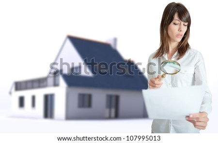 Woman scrutinizing a document with a house in the background - stock photo