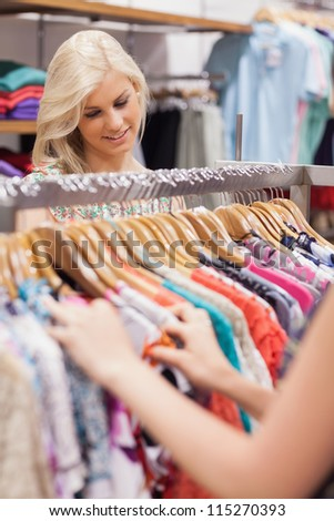 Woman searching at the clothes rack while smiling - stock photo