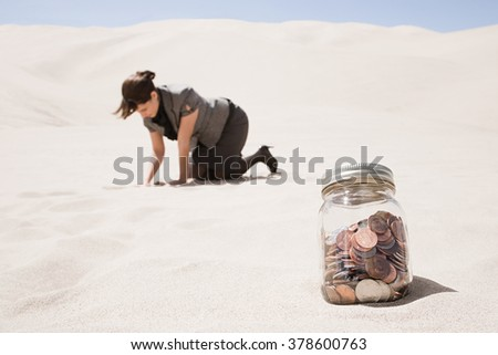 Woman searching for jar of coins in desert - stock photo