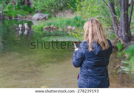 Woman searching network coverage in a river  - stock photo