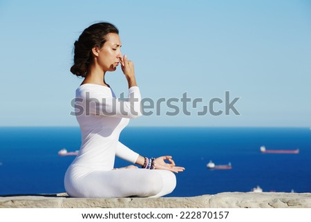 Woman seated in yoga pose on amazing sea background, yoga on high altitude with sea with ships on background, woman meditating yoga enjoying sunny evening, woman makes yoga meditation on high altitude - stock photo