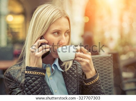 Woman seating in cafe with her phone and coffee. - stock photo