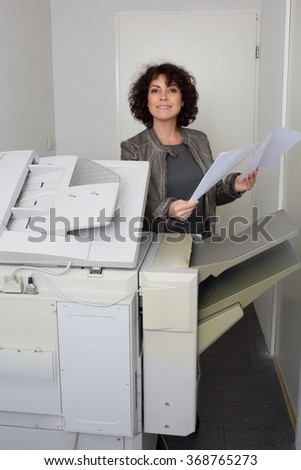 Woman secretary using a printer at work in her office - stock photo