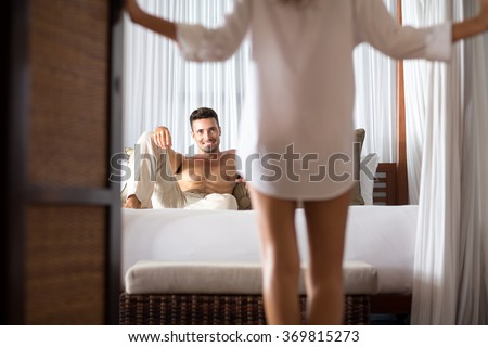 woman seduces her boyfriend in the bedroom, he lying on bed and looking at her  - stock photo