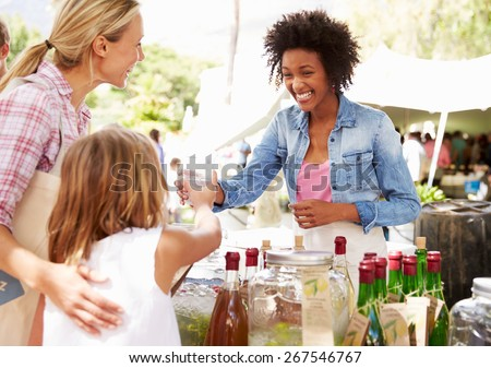 Woman Selling Soft Drinks At Farmers Market Stall - stock photo