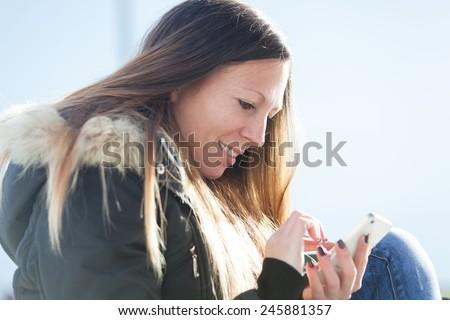 Woman sending a text message  - stock photo