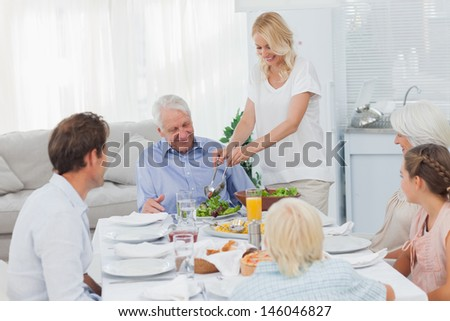 Woman serving salad to grandfather at the dinner table - stock photo