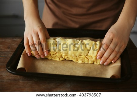 Woman setting an apple roll into baking tray - stock photo