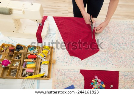 Woman sewing at home with sewing paper - stock photo