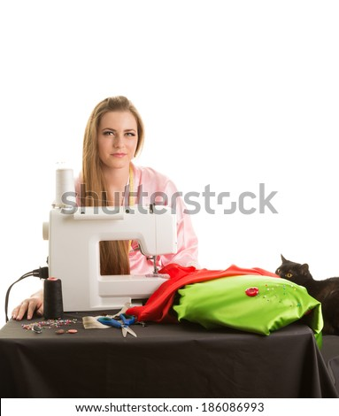 Woman sews on the sewing machine and a black cat watching her - stock photo