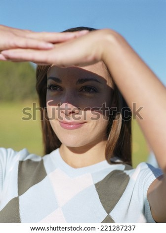 Woman shading eyes with hands - stock photo
