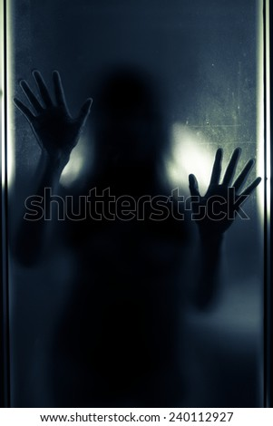 Woman shadow behind translucent mirror,blue tone color filtered. - stock photo