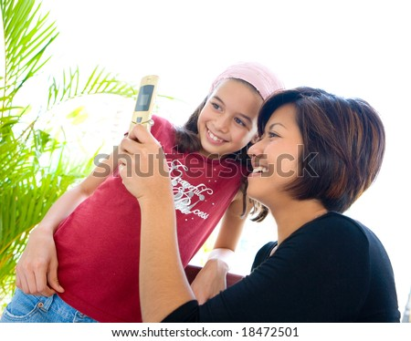 Woman sharing information on her cell phone with a younger child. - stock photo