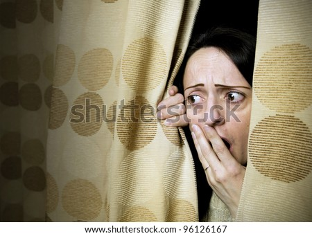 woman shocked at what she sees behind curtains or hiding from intruder - stock photo