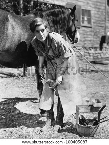 Woman shoeing horse - stock photo