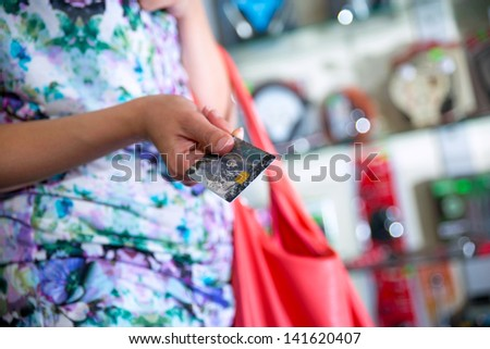 Woman shopping and paying with a debit or credit card - stock photo