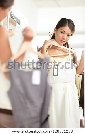 Woman shopping choosing dresses looking in mirror uncertain. Beautiful young multicultural shopper in clothing store. - stock photo