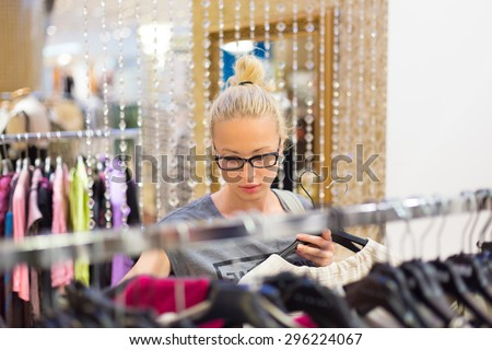 Woman shopping clothes. Shopper looking at clothing indoors in store. Beautiful blonde caucasian female model wearing black glasses. Focus on model. - stock photo