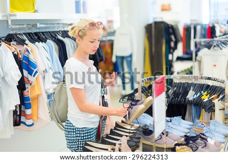 Woman shopping clothes. Shopper looking at clothing indoors in store. Beautiful blonde caucasian female model wearing casual clothes and fashionable sunglasses. Focus on model, shallow depth of field. - stock photo