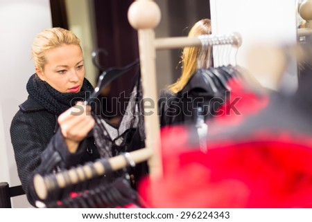 Woman shopping clothes. Shopper looking at clothing indoors in store. Beautiful blonde caucasian female model wearing casual winter clothing and black scarf. - stock photo