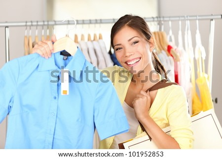 Woman shopping clothes showing shirt in clothing store smiling happy looking at camera. Beautiful young mixed race Asian Chinese / Caucasian young woman shopper. - stock photo