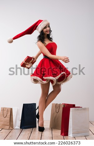 Woman shopping for christmas gifts. Young caucasian girl dancing with shopping bags wearing Santa Claus dress and hat - stock photo