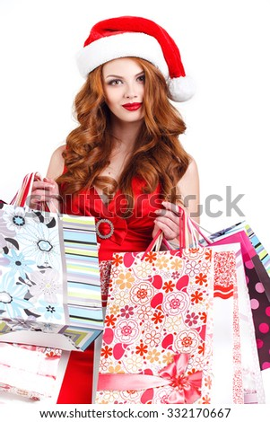 Woman shopping for christmas gifts. Young caucasian girl smiling with shopping bags and santa hat. Copy space on the side. appy shopping Christmas woman with bags white background - stock photo