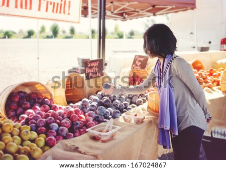 Woman shopping for fruit at an outdoor market - stock photo