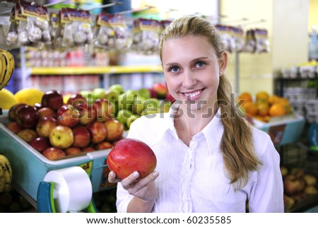 Woman shopping for fruits in the supermarket holding a mango - stock photo