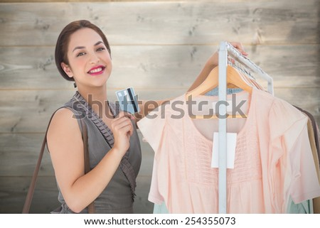 woman shopping with card against bleached wooden planks background - stock photo
