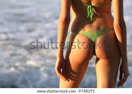 woman shot from back on the beach, wearing bikini triangle. - stock photo
