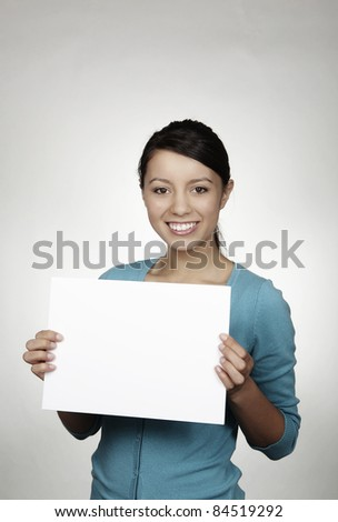 woman shot in the studio holding up white card - stock photo