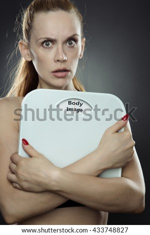 woman shot in the studio, low key lighting holding weight scales with the words body image printed on the scales disk - stock photo