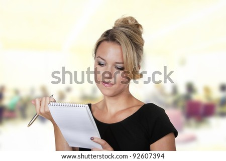 woman shot in the studio on white background holding a pen and note book talking notes - stock photo