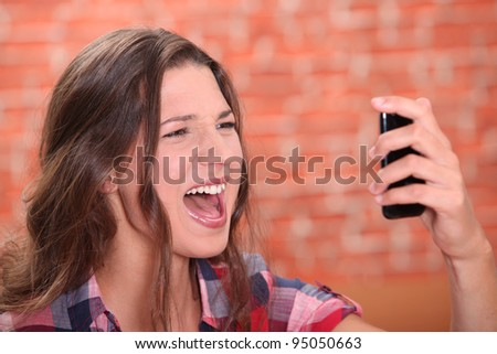 Woman shouting at her cellphone - stock photo