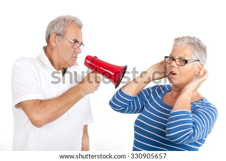woman shouting at the woman with megaphone isolated on White, Senior couple - stock photo