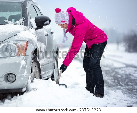 woman shoveling and removing snow from her car, stuck in snow - stock photo