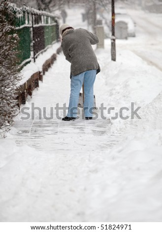 Woman shoveling snow from the sidewalk in front of his house after a heavy snowfall in a city (focus on the fence in the foreground) - stock photo