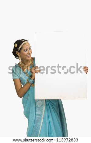Woman showing a blank placard and smiling - stock photo