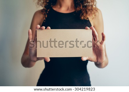 woman showing a brown blank page of clipboard - stock photo