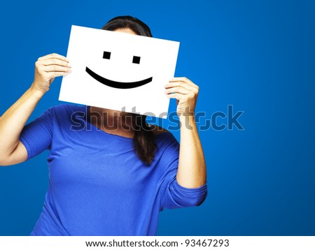 Woman showing a happy emoticon in front of face against a blue background - stock photo