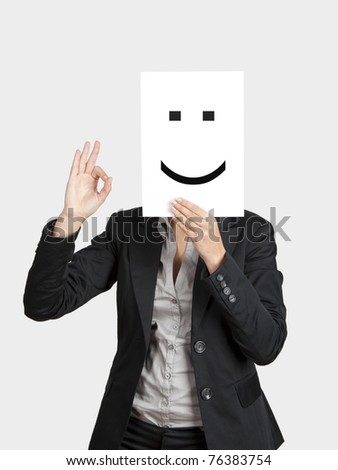 Woman showing a happy emoticon in front of face and making a okay gesture with the right hand - stock photo