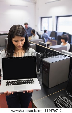 Woman showing a laptop in computer class - stock photo