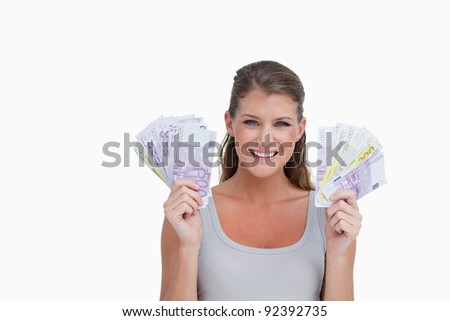Woman showing bank notes against a white background - stock photo