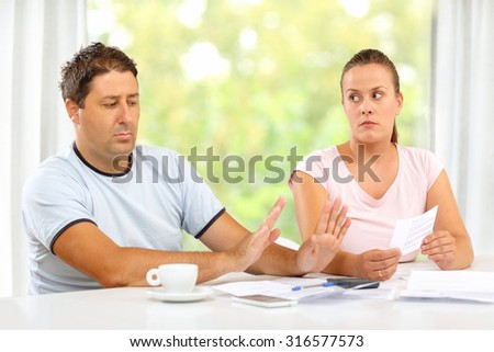 Woman showing bills to her husband, he is gesturing that he has nothing to do with them. - stock photo